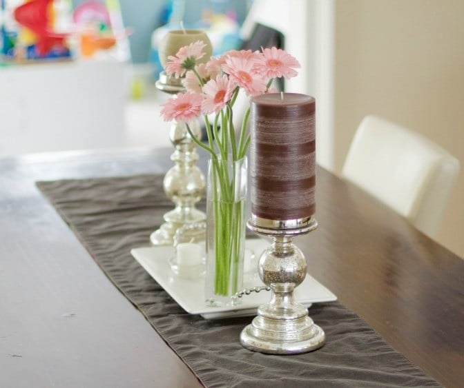 Vase of pink Gerber Daisies and candles on a neutral runner on wooden dining room table #diningroom