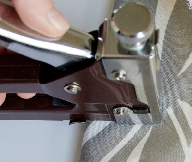 Hand using a staple gun to upholster a chair seat. #upholster
