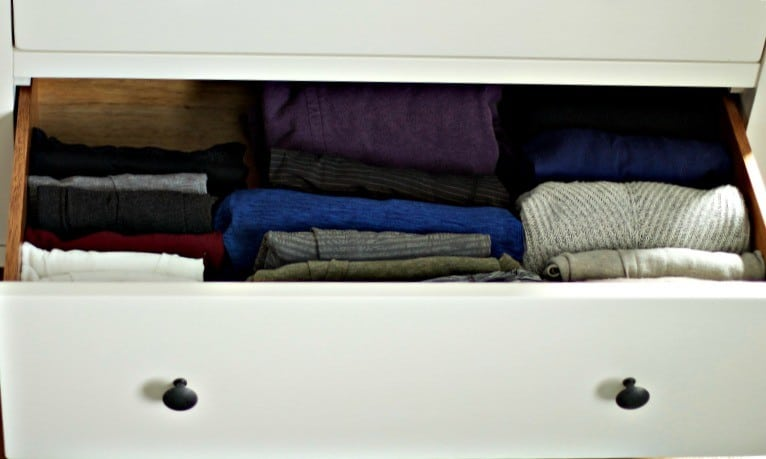 Vertically folded clothing in an open white drawer #folding