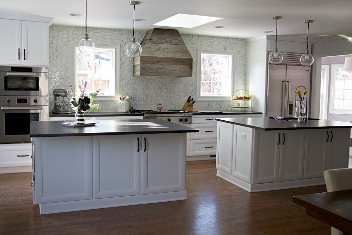Updated kitchen with finished hood, white cabinets, and black countertops #kitchen #farmhouse