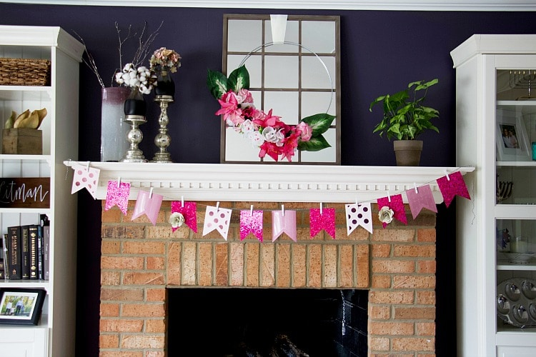 full mantel picture with pink faux flower hoop wreath on mirro and pink banner. Using items found from the Dollar Store, you can create a faux flower hoop wreath in this easy-to-follow tutorial with lots of pictures to help you create this spring trend! #fauxflowers #dollarstore #hoopwreath