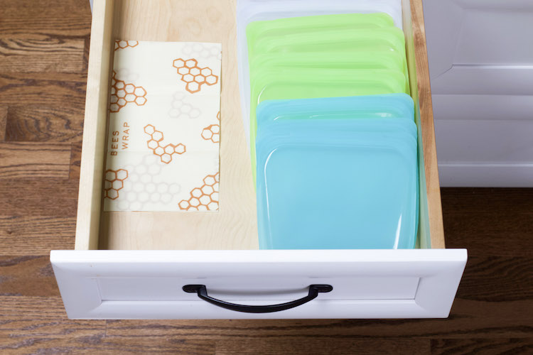 Reusable freezer bags are lined in a shallow drawer along one edge with wax paper on the other edge to demonstrate alternatives to Ziploc bags #sustainable #reusable