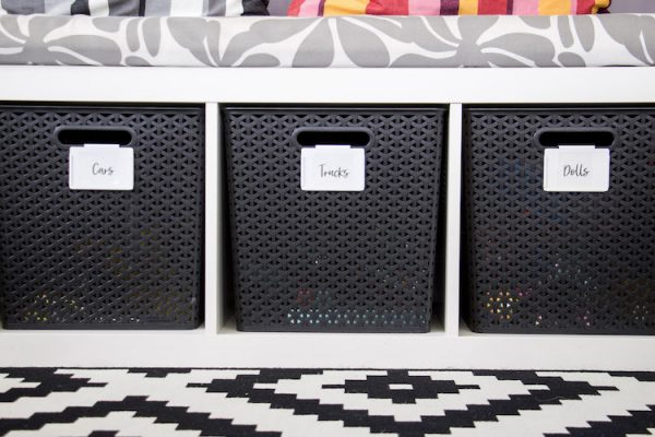 three hand lettered printable stickers labels on black bins in play room. cursive font on white bin clips.