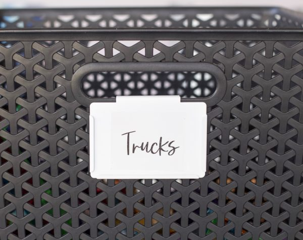 close up of cursive hand lettered printable sticker labels. black bin with white bin clip and black cursive lettering