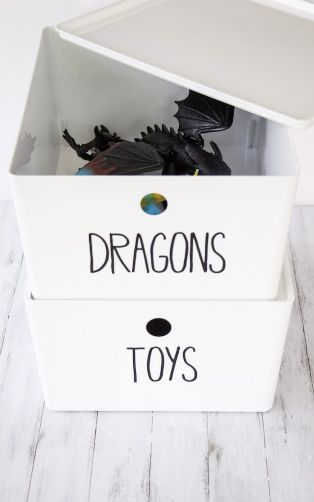 """looking inside two white stacked bins with black lettering that say """"dragons"""" with dragons from the movie How To Train Your Dragon 3 inside"""