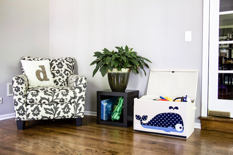 Chair with pillow next to end table with plant and toy chest with whale to hold dress-up clothing in playroom #playspace