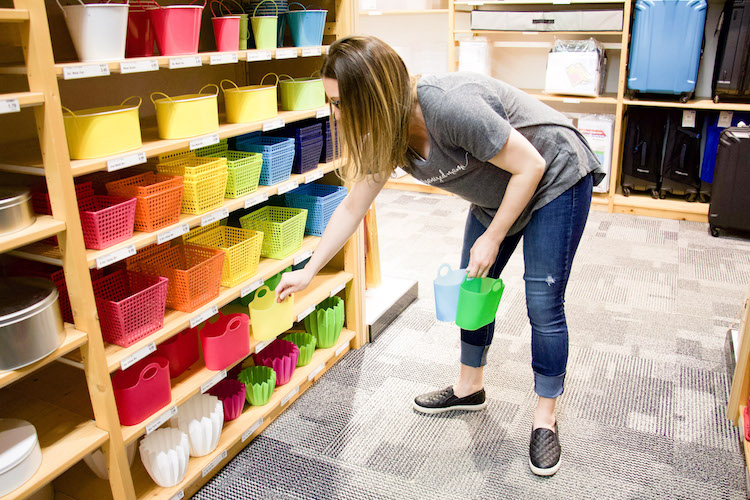 professional organizer shopping at the container store in the party aisle holding mini party totes