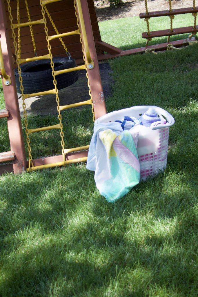 Tote outside next to playground with rolled beach towels to demonstrate towel storage ideas #beachtowels
