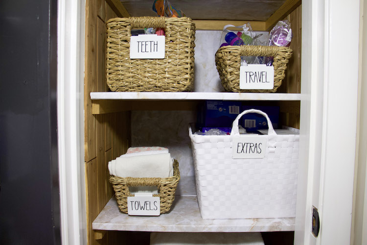 Two shelves in a linen closet with marble shelf liner and labels of extra, teeth, travel, and towels #linenclosets