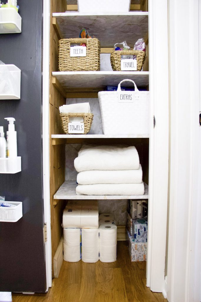 Five shelves of linen closet with marble shelf liner on all shelves and back wall of linen closet #organized
