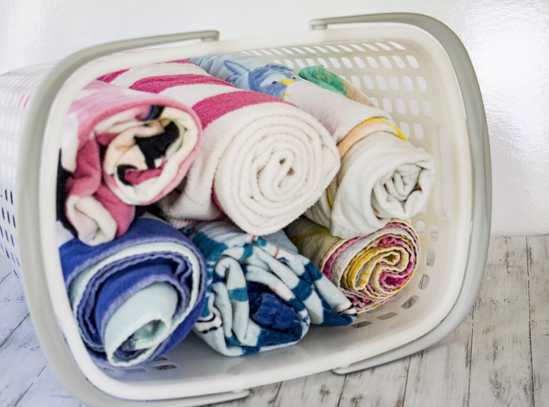 Rolled towels stored in tote from The Container Store to demonstrate towel storage ideas #beachtowels #towelstorage