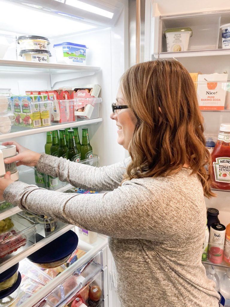 fridge organization with professional organizer finishing up by stacking fridge bins for easy storage