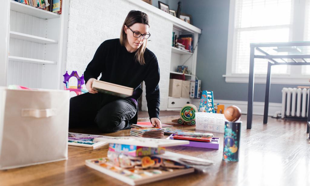 Jessica sitting on the floor organizing kids toys. #organizingkids